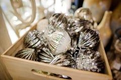 A decoração de vidro da árvore de Natal brinca sob a forma das bolas de prata em uma caixa de madeira fotos de stock royalty free