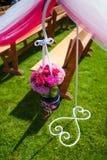 Decoração do casamento das flores perto dos bancos para a cerimônia no parque Imagem de Stock Royalty Free