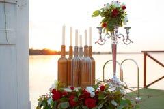 Decoração do casamento - a instalação bonita na tabela pelo mar: velas, garrafas, estatueta Imagem de Stock