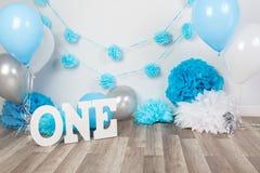 decoração do fundo para a celebração do aniversário com bolo gourmet, letras que dizem um e balões azuis no estúdio imagens de stock royalty free