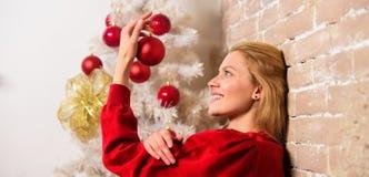 Decoração do inverno Conceito dos feriados de inverno A menina decora a árvore de Natal com ornamento Natal de espera Menina fotografia de stock