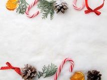 Decoração do Natal Árvore, cones e doces do ramo na neve Vista superior, configuração lisa Imagens de Stock Royalty Free