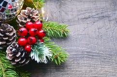 Decoração do Natal com árvore de abeto, as bagas vermelhas, as luzes da festão e os cones do pinho no fundo de madeira velho Fotos de Stock Royalty Free