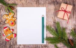 Decoração do Natal com árvore de abeto, chique, caixa de presente e pão-de-espécie Folha de papel vazia em um fundo do Natal Fotografia de Stock Royalty Free