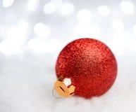 Decoração do Natal com a bola vermelha na neve no fundo borrado com luzes do feriado ano novo feliz 2007 Imagens de Stock