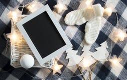 A decoração do Natal com branco fez malha o quadro de madeira dos mitenes e a cesta branca no fundo quadriculado Imagem de Stock Royalty Free
