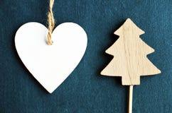 A decoração do Natal com a estatueta de madeira branca da árvore do coração e de abeto no azul sentiu o fundo Fotos de Stock Royalty Free
