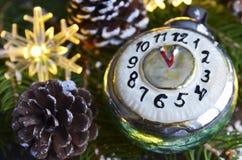 Decoração do Natal com o brinquedo retro do Natal do despertador, os cones do pinho e as luzes da festão no fim de madeira velho  Fotos de Stock