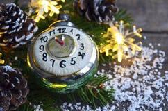 A decoração do Natal com o brinquedo retro do Natal do despertador, os cones do pinho e a festão ilumina-se no fundo de madeira v Foto de Stock Royalty Free
