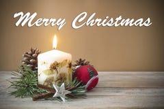 Decoração do Natal com vela, pinho, quinquilharia, com texto no ` inglês do Feliz Natal do ` no fundo de madeira Imagens de Stock Royalty Free