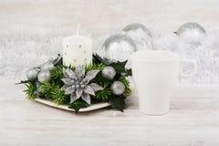 Decoração do Natal com vela, ramo do abeto e caneca de café branco no fundo de madeira branco Modelo da caneca Imagem de Stock