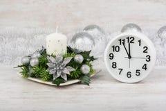 Decoração do Natal com vela, ramo do abeto e pulso de disparo no fundo de madeira branco Imagem de Stock