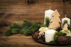 Decoração do Natal - compoition das velas, ramos, pedras no fundo de madeira Fotos de Stock