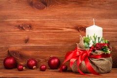 Decoração do Natal - composição do Natal com saco, vela branca e bolas no fundo de madeira Fotografia de Stock