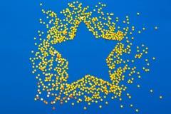 A decoração do Natal de confetes dourados stars contra o backg azul Fotos de Stock