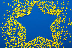 A decoração do Natal de confetes dourados stars contra o backg azul Fotografia de Stock