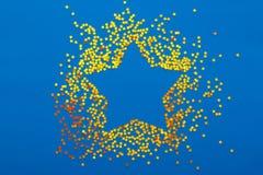 A decoração do Natal de confetes dourados stars no fundo azul Imagens de Stock Royalty Free