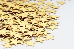 Decoração do Natal de estrelas douradas dos confetes contra fotografia de stock royalty free