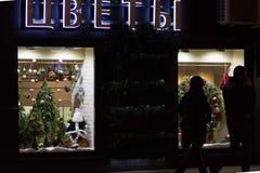 Decoração do Natal em uma janela da loja Boneca de Papai Noel, árvore de Natal, peúga, grinalda do feriado O ` da palavra floresc fotos de stock