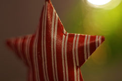Decoração do Natal Estrela vermelha que pendura na árvore do xmas luzes Fundo Bokeh Fotos de Stock