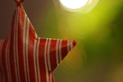 Decoração do Natal Estrela vermelha que pendura na árvore do xmas luzes Fundo Bokeh Imagens de Stock Royalty Free