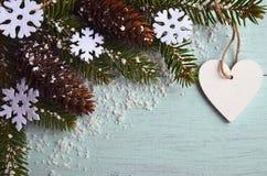 Decoração do Natal Flocos de neve decorativos, cones de abeto, coração e ramo de árvore nevado do abeto na luz - fundo azul com c Imagens de Stock Royalty Free