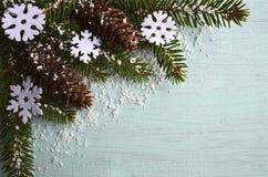 Decoração do Natal Flocos de neve decorativos de feltro, cones de abeto e ramo de árvore nevado do abeto na luz - fundo azul com  Fotografia de Stock