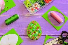 Decoração do ovo da páscoa com teste padrão de flores Ovo de feltro, tesouras, molde de papel, linha, caixa com beades na tabela  imagem de stock
