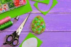 Decoração do ovo da páscoa com teste padrão de flores Decoração do ovo de feltro, tesouras, molde de papel, linha, dedal, caixa c imagens de stock royalty free