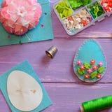 Decoração do ovo da páscoa de feltro com grânulos plásticos Decoração do ovo de feltro, molde de papel, dedal, linha na tabela de imagem de stock