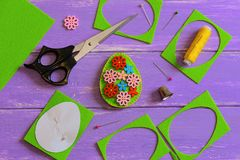 Decoração do ovo da páscoa de feltro Ovo da páscoa feito a mão de feltro com os botões de madeira da flor Sucata de feltro, tesou foto de stock