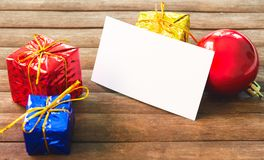 A decoração do presente do Natal e esvazia o cartão de papel na tabela de madeira Modelo do cartão de Natal Fotografia de Stock Royalty Free