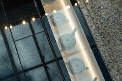 Decoração do shopping - potenciômetros do chá sob um assoalho de vidro foto de stock royalty free