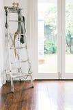 A decoração do vintage de uma escada velha, o sino da exploração agrícola e a corda iluminam-se em um co Fotos de Stock