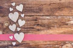 Decoração dos corações na beira vermelha da fita e no fundo de madeira fotos de stock royalty free