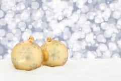 A decoração dourada do fundo das bolas do Natal com neve ilumina-se Imagens de Stock Royalty Free