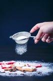 Decoração e biscoitos do Natal Mão da mulher que polvilha o açúcar no cookies Farinha e especiarias para um cozimento em um backg Foto de Stock