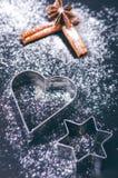 Decoração e biscoitos do Natal Mão da mulher que polvilha o açúcar no cookies Farinha e especiarias para um cozimento em um backg Imagem de Stock Royalty Free