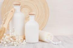 Decoração elegante macia do banheiro das garrafas brancas com pente, flores dos cosméticos na placa de madeira branca, zombaria a Foto de Stock Royalty Free