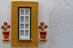 Decoração em uma parede: Janela e vaso de flores amarelos Imagens de Stock Royalty Free