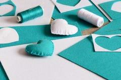Decoração enchida pequena dos corações Corações feitos do feltro, da linha, das folhas de feltro e das sucatas, agulha na tabela  Imagem de Stock