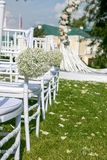 Decoração exterior da cerimônia de casamento do verão As cadeiras brancas decoradas com as bolas do gypsophila no fundo do arco p fotos de stock