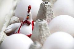 Decoração feliz do galo da Páscoa e ovos crus fotografia de stock royalty free