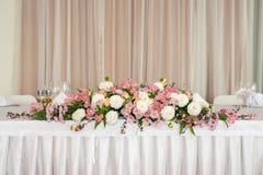 Decoração floral do casamento bonito em uma tabela em um restaurante Toalhas de mesa brancas, sala brilhante imagem de stock