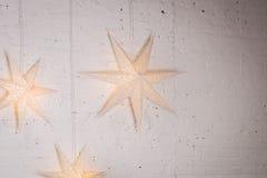 Decoração grande das estrelas na parede branca Estrelas brilhantes decoração da remoção de ervas daninhas com as estrelas grandes imagem de stock royalty free