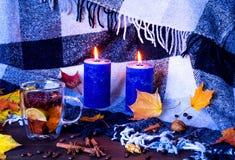 Decoração home do outono, copo com chá cura e varas de canela entre a queimadura de velas azuis e das folhas amarelas brilhantes  foto de stock royalty free