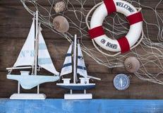 Decoração marítima com escudos, estrela do mar, navio de navigação, rede de pesca na madeira azul da tração imagem de stock royalty free