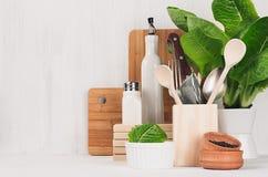 Decoração moderna da cozinha - utensílios de madeira bege, placas de corte marrons, planta verde no fundo de madeira branco da lu fotos de stock