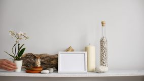 Decoração moderna da sala com modelo da moldura para retrato Prateleira contra a parede branca com vela, vidro e as rochas deco