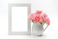 Decoração, moldura para retrato e copo home com rosas Imagens de Stock Royalty Free